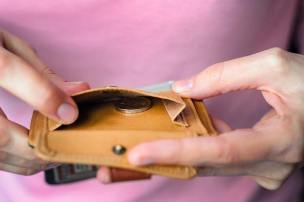 Одна монета в пустом кошельке в руках женщины.