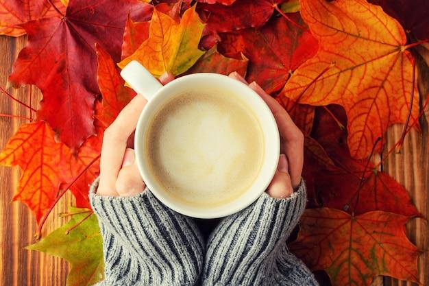 女性がバックグラウンドで一杯のコーヒーを保持しています。