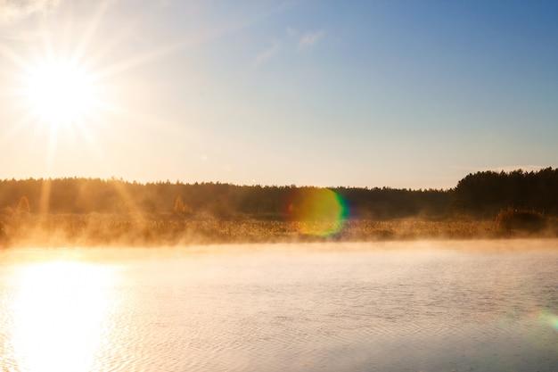日の出や日没の霧の川。水の上の霧