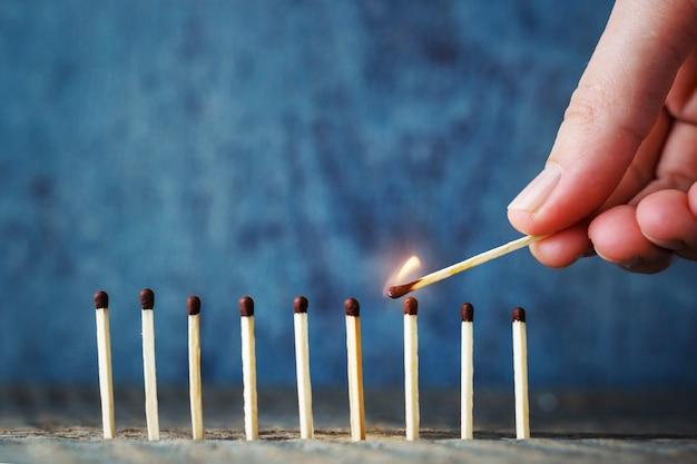 手持ちの火のついた試合は、火の上に別の試合を設定しようとします。