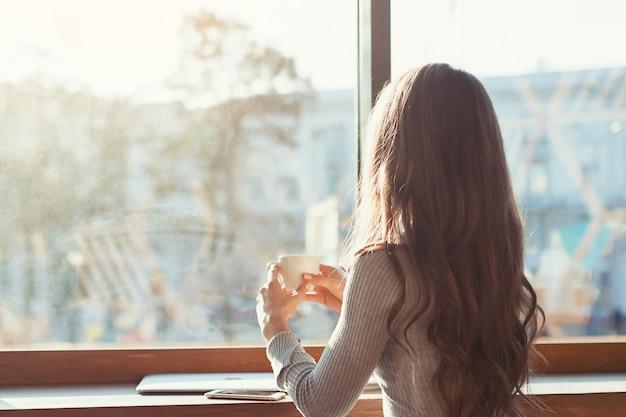 カフェの女性はテーブルに座って、コーヒーを飲みます