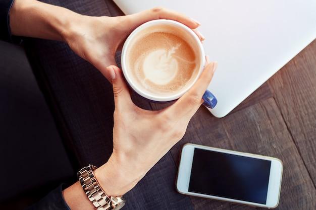 少女は一杯のコーヒーカプチーノラテアートを持っています。