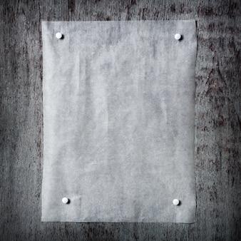 一枚の紙が灰色の木製の背景に固定されています。