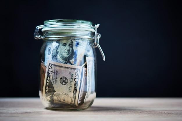 コピースペースを持つガラス瓶に米ドル紙幣。