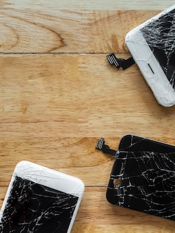 木製の背景にひびの入ったスマートフォンの画面