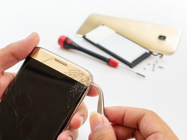 割れたスマートフォンの画面を脱いで技術者の手
