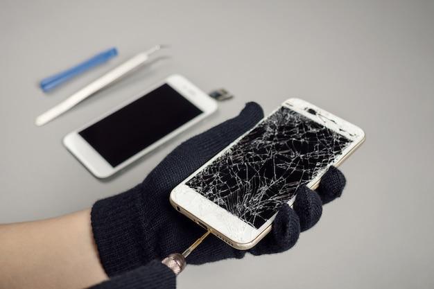 机の上の壊れたスマートフォンを修復する技術者