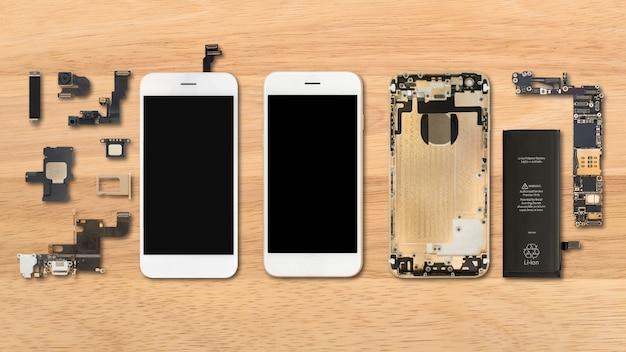 木製の背景にスマートフォンの部品