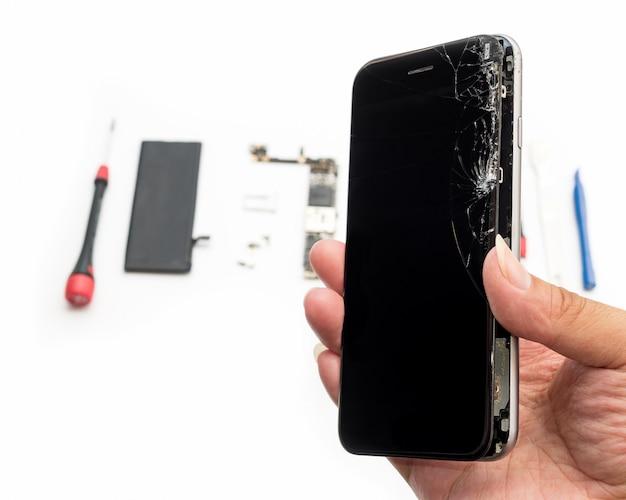 白い背景の上の壊れたスマートフォンを修復します。