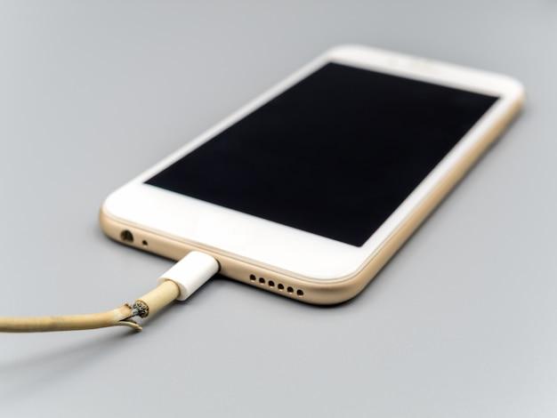 Крупным планом поврежденный кабель зарядного устройства для смартфона