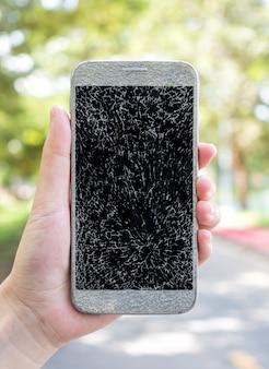 古い壊れてひびの入った画面のスマートフォン