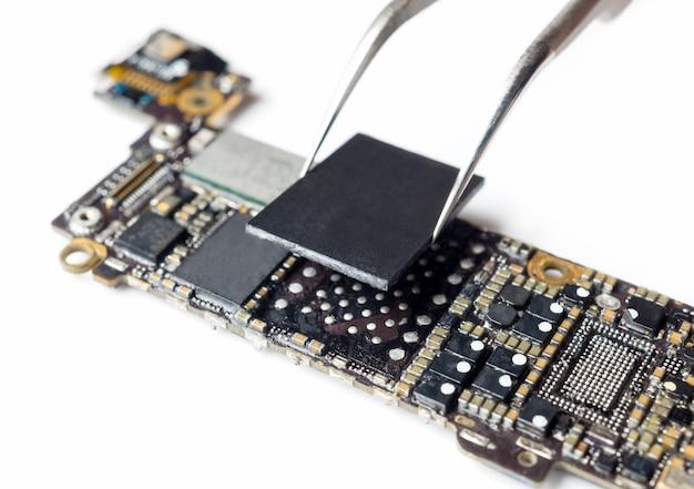 スマートフォンのマザーボードのフラッシュストレージを交換する技術者