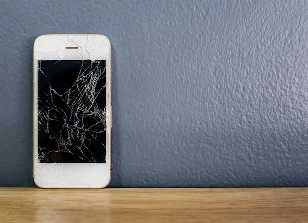 灰色の壁にもたれて壊れたスマートフォン