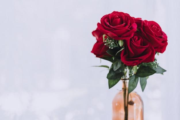 ボトルの花瓶に赤いバラの花束