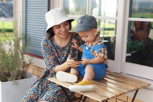 スマートフォンをしている母親と赤ちゃんの少年