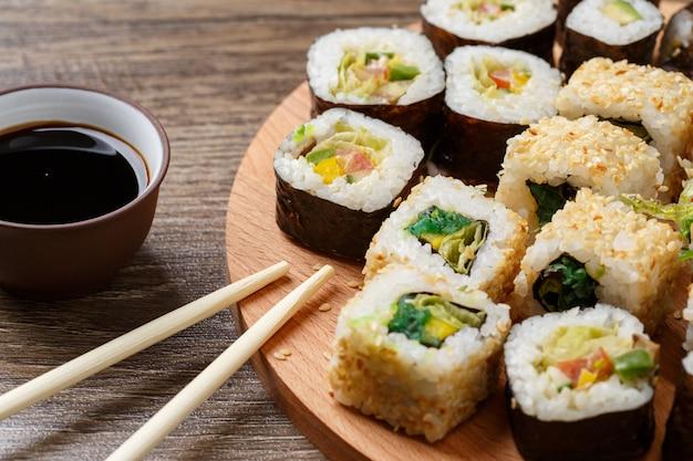 黒の木製テーブルの上のサーモンと熱いお茶の式で巻き寿司