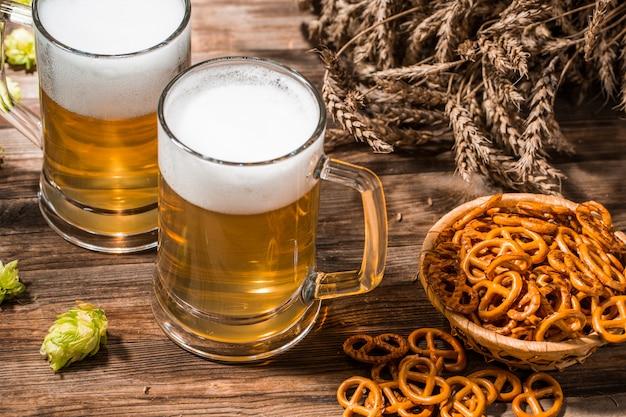 Кружки пенистого пива, хмеля, кренделя и пшеницы на деревянный стол