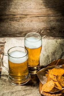 マグカップ、木製の背景上のガラスのビール
