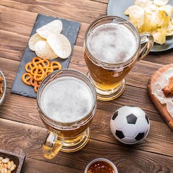 サッカーの試合を観戦するためのテーブルの前菜とビール。