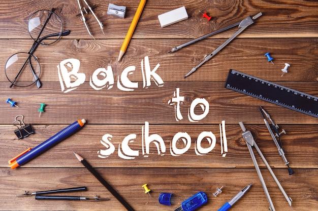 テキスト-木製のテーブルに学校と学生の資料に戻る。