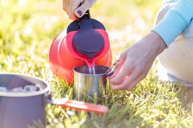 Девушка наливает воду из чайника
