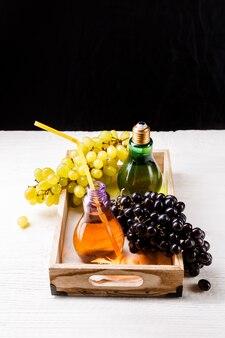 Изображение деревянный поднос с зеленым и черным виноградом, две бутылки сока