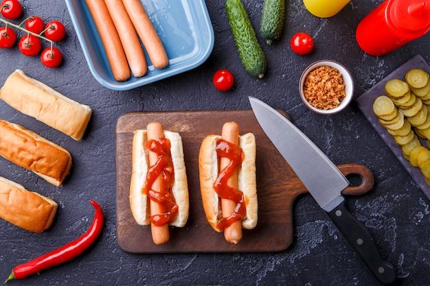Фотография сверху двух хот-догов на разделочной доске на столе с сосисками