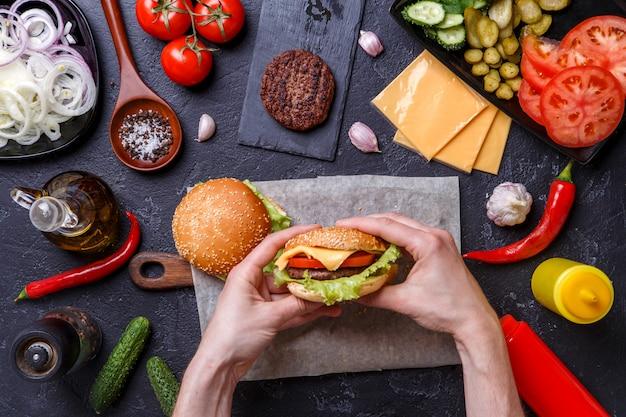 Фотография сверху двух гамбургеров, человеческих рук, перца чили,