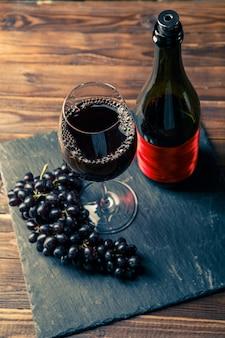 Бутылка красного вина, бокал с вином, черный виноград на каменной доске