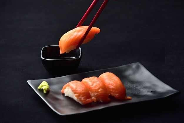 Суши из лосося с нигири и соусом васаби с палочками для еды на черном клапане.