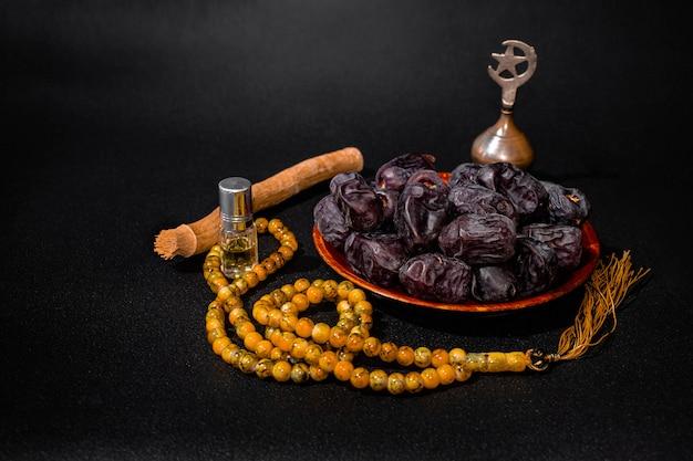 ラマダンカリームムバラクイスラムの暗い表面、日付、祈りのビーズ、ミスワク、イタルとアンチモン、コピースペース