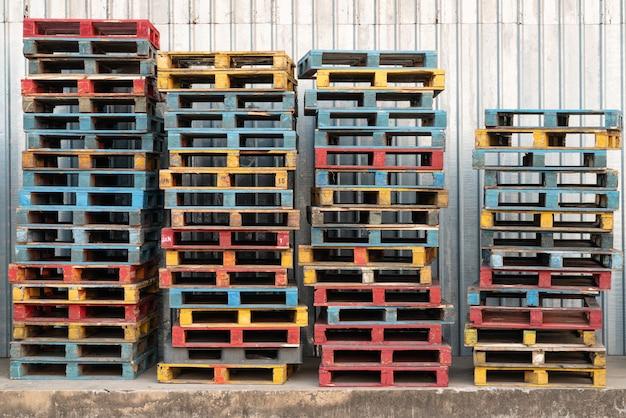 カラフルな大まかな木製パレット背景の倉庫での積み上げ