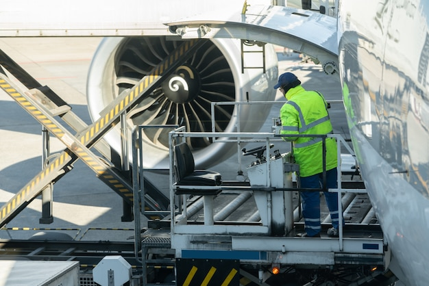 荷台の積荷人は貨物航空機に航空貨物を積み込みます。