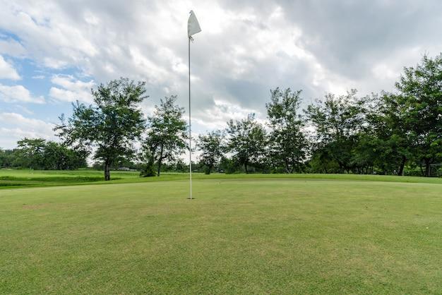 ゴルフ場の穴に白い旗。ゴルフ場の美しい風景。