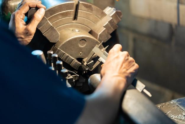 プロの機械工:旋盤研削盤を操作する人