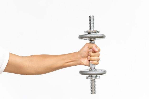 コピーテキストスペースを持つ白のダンベルでのエクササイズ筋肉男の腕