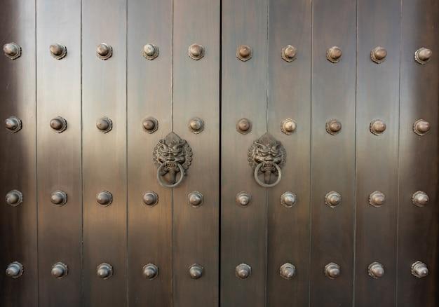 チーク材のドアの金属東洋ライオンハンドル。アンティークオリエンタルドアノッカー。