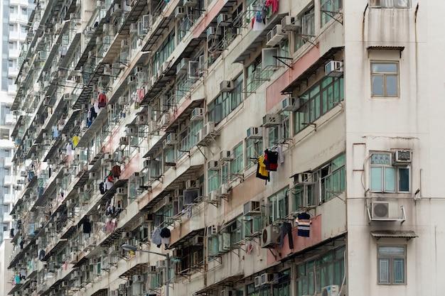 Старая квартира с повесить сушить одежду, экстерьер старого жилого дома в дневное время в гонконге.