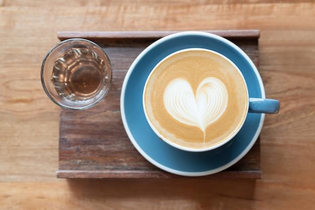木製のテーブルにバリスタアートハート形泡によってお茶のカップとホットコーヒーカップの平面図です。