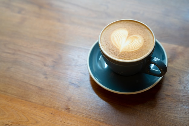 木製のテーブルにバリスタアートハート泡とホットコーヒーカップの平面図です。