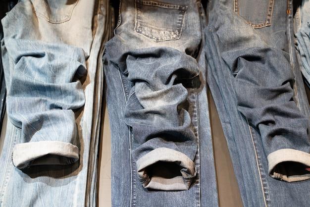 Модные разные джинсы. джинсы сложены на столе.