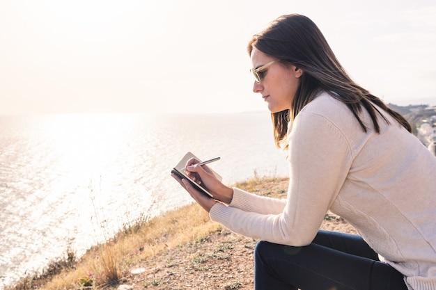 春の海の前にメモ帳で書く若い女性