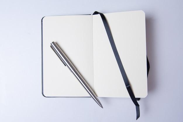 白いテーブルに空白のメモ帳を書く準備ができて