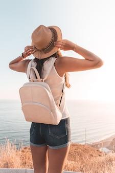 Девушка перемещения или отпуска с рюкзаком и шляпой смотря горизонт