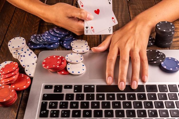 ポーカーチップとベットまたはプレイ用のカードを備えたコンピューターの平面図。