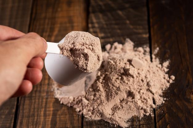 ミルクセーキを準備するために木製のテーブルでホエイプロテインのスクープを測定します。
