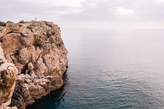 下の海と崖に沈む夕日。スペイン、アンダルシア、グラナダのビーチ。