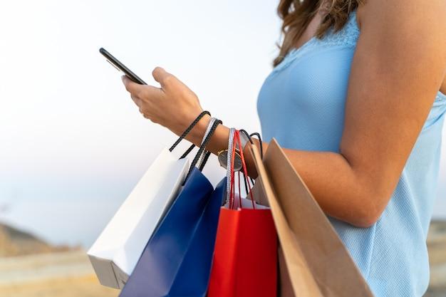 Молодая женщина, используя ее мобильный телефон с некоторыми сумок. торговая концепция