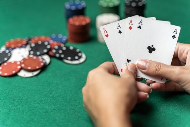 Стек фишек и рука женщины с четырьмя тузами на столе. концепция игры в покер
