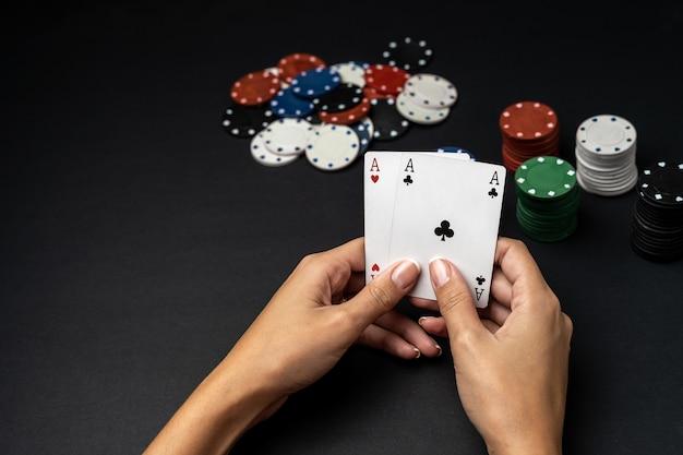 Стек фишек и рука женщины с двумя тузами на столе. концепция игры в покер